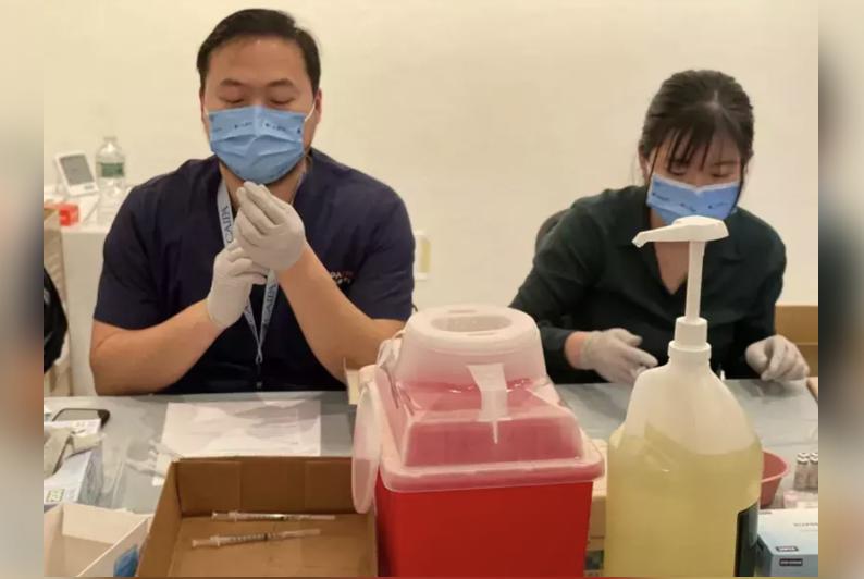 「亞美醫師協會」的醫護人員為民眾準備輝瑞疫苗的注射。